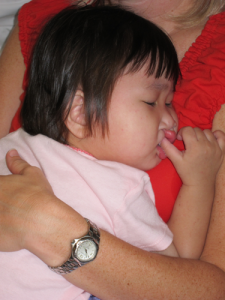 Sleeping on Mommy sucking her thumb